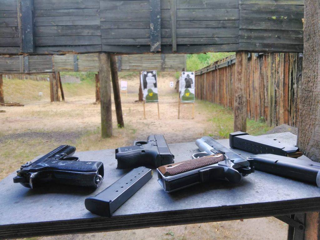 Egzamin na patent strzelecki wygląda troszkę inaczej (strzela się do innych tarcz), ale regulamin dopuszcza przeprowadzenie go z takich pistoletów. Na fotografii widać pistolety Glock, 1911 i Beretta 92 leżące na stole na strzelnicy. W tle tarcze.